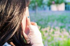 Unga studentkvinnor som kallar på smartphonen, medan handledhanden smärtar begreppssoffa som tycker om den moderna nätt vita kvin Royaltyfri Bild