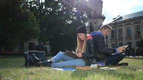 Unga studentpar som studerar i parkeragräsmattan stock video