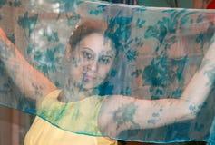 Unga 20-talflickablickar på kameran till och med genomskinlig siden- hals Royaltyfri Foto