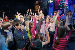 Unga teaterbesökare barn som håller ögonen på entusiastiskt barns teatern Smeshariki för juldockteaterföreställning Arkivbild
