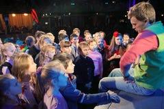 Unga teaterbesökare barn som håller ögonen på entusiastiskt barns teatern Smeshariki för juldockteaterföreställning Royaltyfri Bild