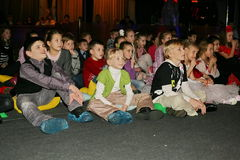 Unga teaterbesökare barn som håller ögonen på entusiastiskt barns teatern Smeshariki för juldockteaterföreställning Royaltyfria Foton