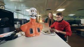 Unga teknikerer behandlar en cyborg in i att flytta dess ansikts- organ stock video