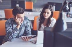 Unga tillfälliga affärspar genom att använda datoren i kontoret Coworking idérik chef som visar ny startup idé Fotografering för Bildbyråer