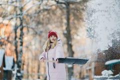 Unga tonåriga flickarengöringar snöar nära huset som rymmer en skyffel, och skoveln spenderar tid Royaltyfri Fotografi
