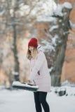Unga tonåriga flickarengöringar snöar nära huset som rymmer en skyffel, och skoveln spenderar tid Fotografering för Bildbyråer