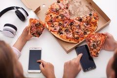 Unga tonåringar som kontrollerar deras telefoner, medan äta pizza arkivbilder