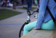 Unga tonårs- flickor med ett telefonsammanträde bredvid en cykel royaltyfri bild