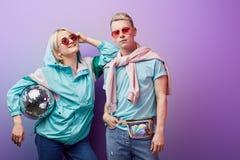 Unga trendiga par av dansare som poserar med diskobollen på violett bakgrund arkivbild