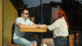 Unga trevliga par som sitter i kafét som slås in i slags tvåsittssoffafilten som dricker te Kärlekshistoria av en flicka och en p lager videofilmer