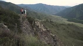 Unga turister med ryggsäckar tycker om sikten av bergen Handelsresande står på kanten av klippan stock video