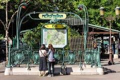 Unga turister på ingången till den Paris Metropolitain subwaen Royaltyfri Foto
