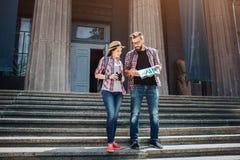 Unga turister står på trappa och lok på översikt De studerar som det, koncentreras grabben ler kvinnabarn Hon rymmer arkivfoto