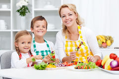 Unga ungar med deras moder i köket Royaltyfria Bilder