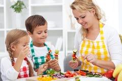 Unga ungar med deras moder i köket - förbereda en vegeta Arkivbild