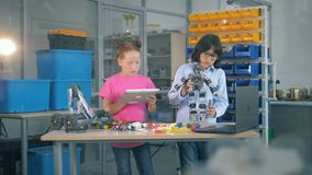 Unga ungar som tillsammans arbetar i ett laboratoriumrum Skolbarn använder laboratoriumutrustning för att konstruera en leksakrob