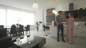 Unga upphetsade lyckliga par som ser runt om den nya lägenheten för inre modern moderiktig designinflyttning för kök i skottet 4k lager videofilmer