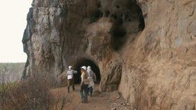 Unga utforskare i hjälmar skriver in till den stora mörka grottan med ficklampor arkivfilmer