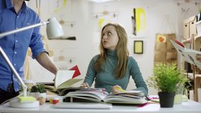Unga utmattade läseböcker för kvinnlig student och göraläxa, medan andra kommer med hennes andra böcker stock video
