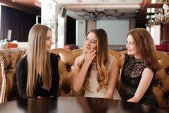 Unga vänner är diskutera och skratta i ett kafé royaltyfria bilder