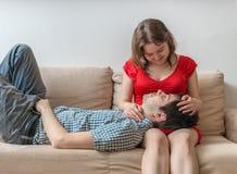 Unga vänner - förälskade par är avslappnande på soffan och att se i ögon Royaltyfria Bilder