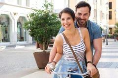 Unga vänner kopplar ihop att rida en cykel i gatan fotografering för bildbyråer