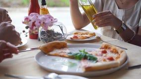 Unga vänner möter i en restaurang som äter pizza som dricker alkohol och träffande berättelser arkivfilmer