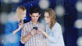 Unga vänner - man, och två kvinnor i en nattklubb använder smartphonen som håller ögonen på tillsammans något att intressera på s arkivfilmer