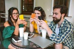 Unga vänner med smartphones och bärbara datorn i kafé med kaffe Arkivbilder