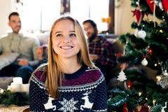 Unga vänner på den dekorerade julgranen som firar jul royaltyfri fotografi