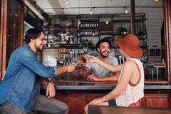 Unga vänner på kafét som rostar drinkar Royaltyfri Foto