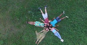 Unga vänner som bildar en stjärna, formar att ligga i gräs och att vinka till kameran stock video