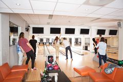 Unga vänner som bowlar i klubba Arkivbilder