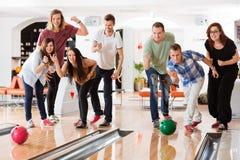 Unga vänner som bowlar medan hurra för folk Arkivbild