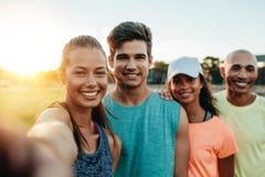 Unga vänner som gör selfie, når att ha joggat royaltyfri foto