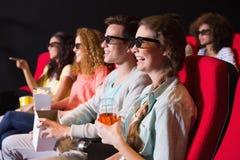 Unga vänner som håller ögonen på en film 3d Royaltyfri Fotografi