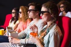 Unga vänner som håller ögonen på en film 3d Arkivbilder