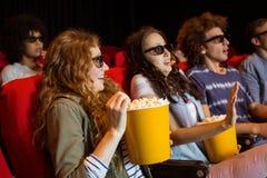Unga vänner som håller ögonen på en film 3d Royaltyfri Foto