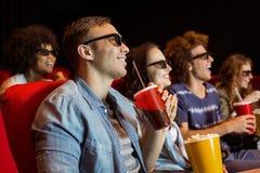 Unga vänner som håller ögonen på en film 3d Royaltyfria Bilder