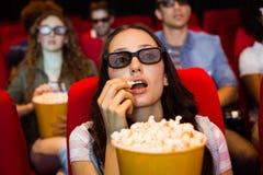 Unga vänner som håller ögonen på en film 3d Arkivfoto