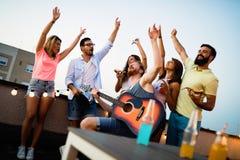 Unga vänner som har gyckel på ett takparti och att spela gitarren, att sjunga, att dansa och att dricka royaltyfri fotografi