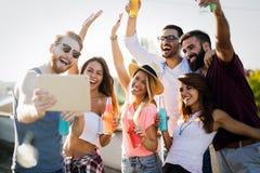Unga vänner som har gyckel på ett takparti och att spela gitarren, att sjunga, att dansa och att dricka royaltyfri bild