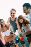 Unga vänner som har gyckel på ett takparti och att spela gitarren, att sjunga, att dansa och att dricka royaltyfri foto