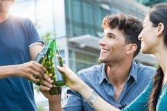 Unga vänner som rostar med öl Arkivfoton