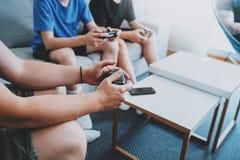 Unga vänner som sitter på en soffa i vardagsrum och spelar videospel Begrepp för avslappnande tid för familj hemmastatt Arkivfoton