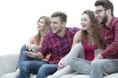 Unga vänner som sitter på soffan och rotar för deras favorit- lag fotografering för bildbyråer