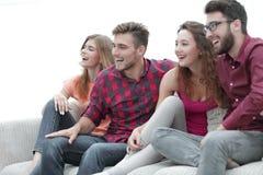 Unga vänner som sitter på soffan och rotar för deras favorit- lag arkivfoto