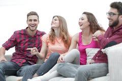 Unga vänner som sitter på soffan och rotar för deras favorit- lag royaltyfri fotografi