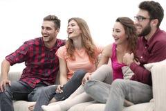 Unga vänner som sitter på soffan och rotar för deras favorit- lag arkivfoton