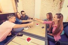 Unga vänner som skrattar och rostar i kafé Royaltyfria Bilder